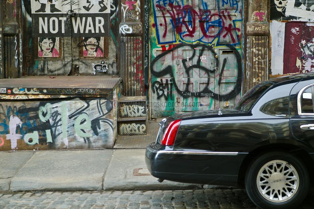 car with sidewalk and graffiti